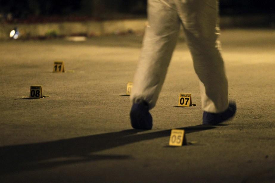 Un policier inspecte la scène d'un double meurtre... (Photo: Reuters)