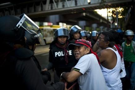 Un «chemise rouge» parle avec des policiers anti-émeutes.... (Photo AFP)