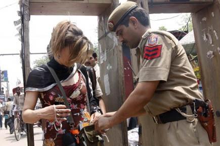 Un policier fouille le sac d'une touriste dans... (Photo AP)