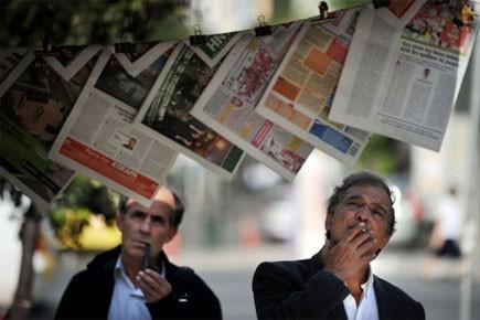 Deux hommes grecs regardent les unes des différents... (Photo: AFP)