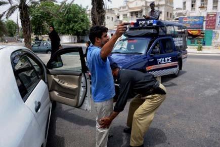 Un policier pakistanais fouille un homme lors d'un... (Photo: Asif HASSAN, afp)