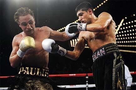 Paulie Malignaggi encaisse les coups d'Amir Khan.... (Photo: AP)