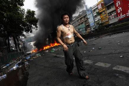 Un supporteur des chemises rouges marche devant un... (Photo: Jerry Lampen, Reuters)