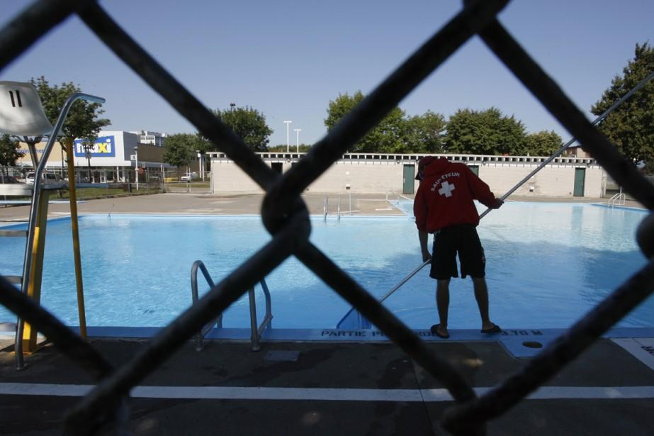Un sauveteur nettoie une piscine de Montréal.... (Photo: François Roy, archives La Presse)