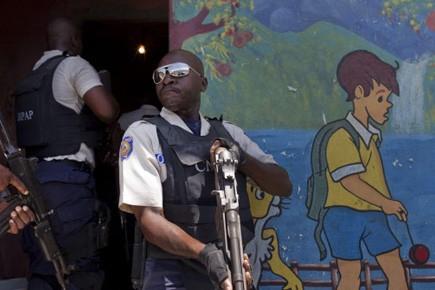 Des policiers haïtiens recherchent des gangs, à Port-au-Prince,... (Photo AP)