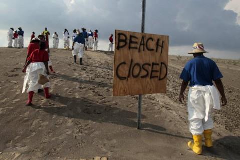 Des employés tentent de nettoyer la plage de... (Photo: AP)