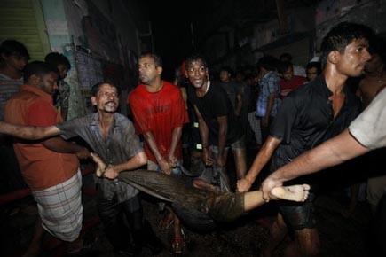 Des secouristes transportent le corps d'une victime extirpé... (Photo: Andrew Biraj, Reuters)