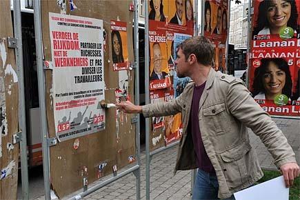 Un homme pose des affiches électorales à Bruxelles.... (Photo: AFP)
