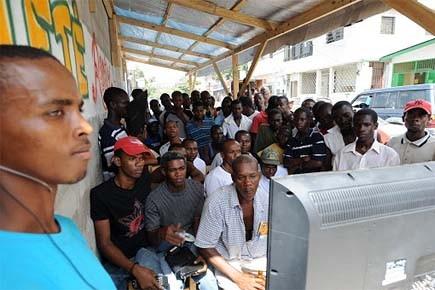 Des Haïtiens s'offrent un répit et regardent la... (Photo: AFP)