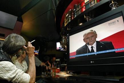 Un homme regarde à la télévision Jaroslaw Kaczynski,... (Photo: Reuters)
