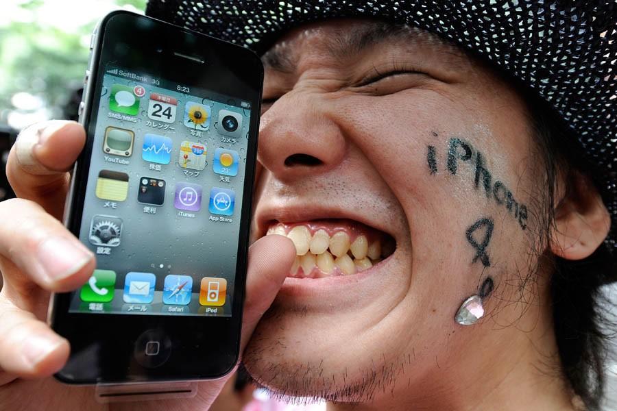 Un jeune homme montre le iPhone 4 qu'il... (Photo: AFP)