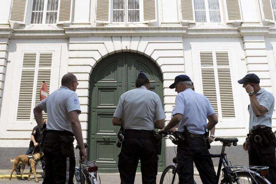 Des policiers font le guet devant les locaux... (Photo: Reuters)