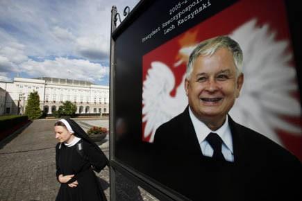 Une religieuse passe devant une affiche du président...