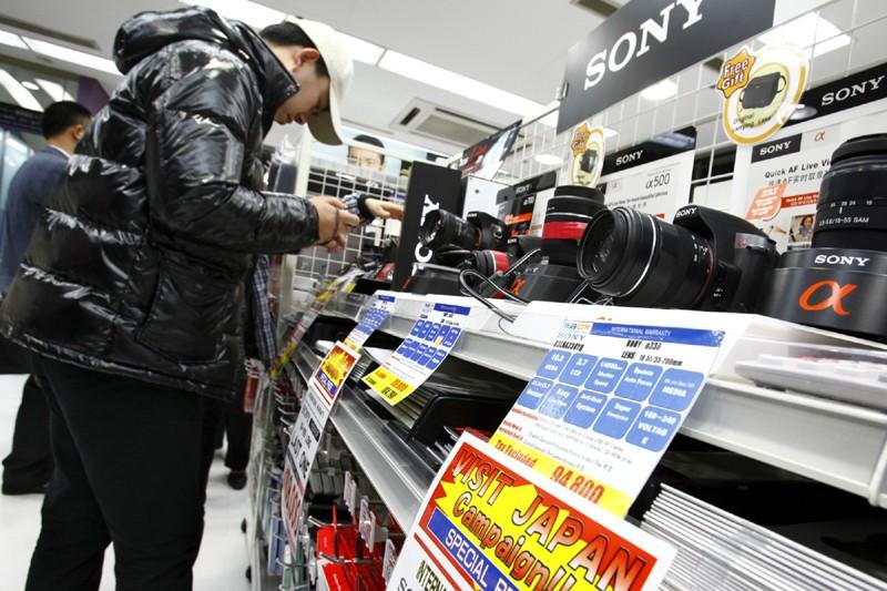 Un touristechinoisexamine un appareil photo numérique japonais dans... (Photo Shizuo Kambayashi, AP)