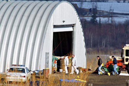 Des enquêteurs passent la ferme de Roszko au... (Photo: Jeff McIntosh, archives PC)