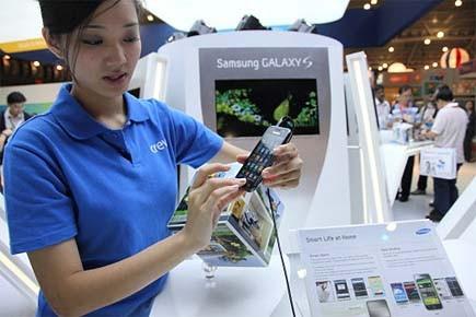 Une employée de Samsung manipule un téléphone intelligent... (Photo: AFP)