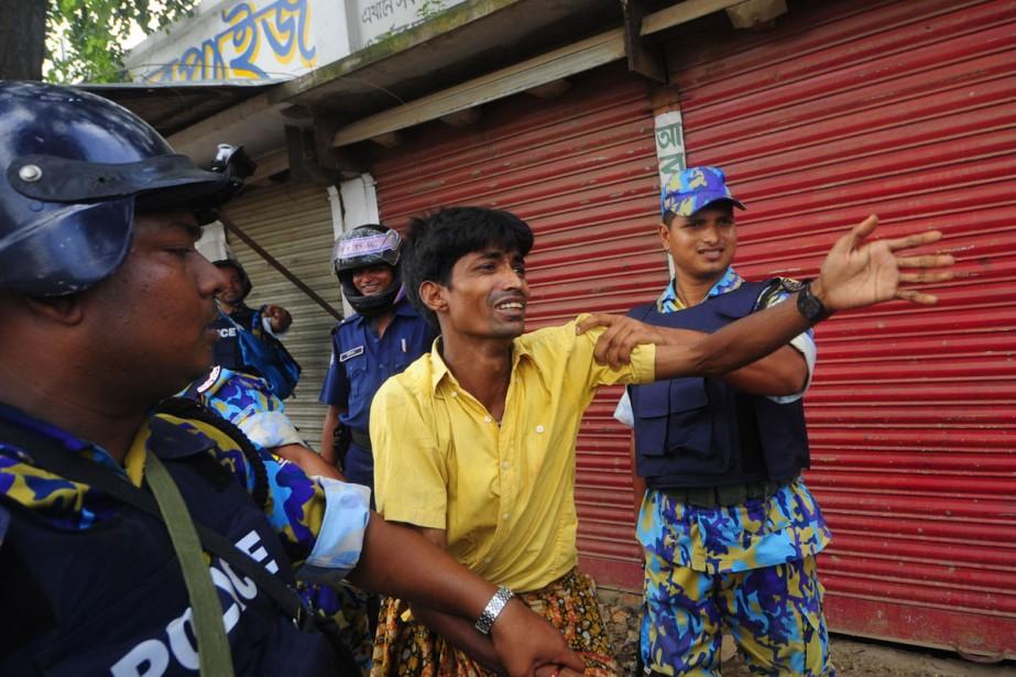 Un travailleur de l'industrie du textile est arrêté... (Photo: AFP)