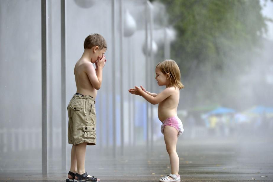 Des enfants profitent des jeux d'eau pour se... (Photo: AFP)