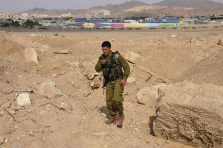 Un soldat israélien cherche des débris de roquettes.... (Photo: AP)