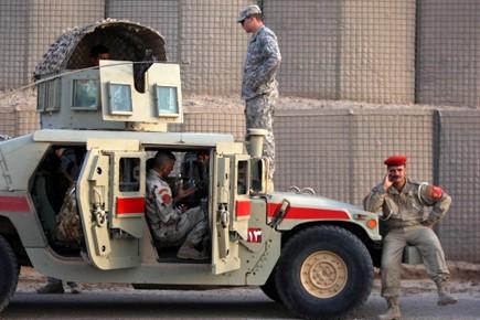 Un soldat se tient debout sur unevoiture depolice... (Photo: AFP)