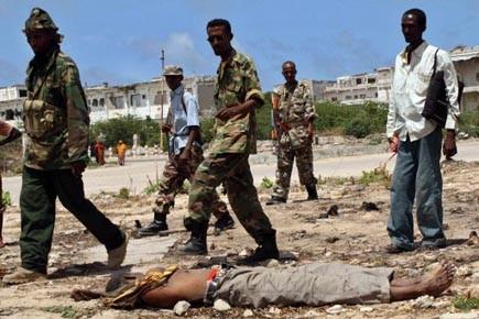 Des soldats somaliens marchent devant le cadavre d'un... (Photo: Abdurashid Abdulle, AFP)