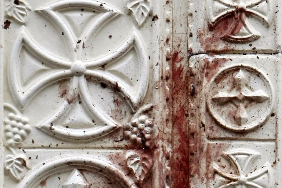 Du sang tache la porte de l'église des... (Photo: AFP)