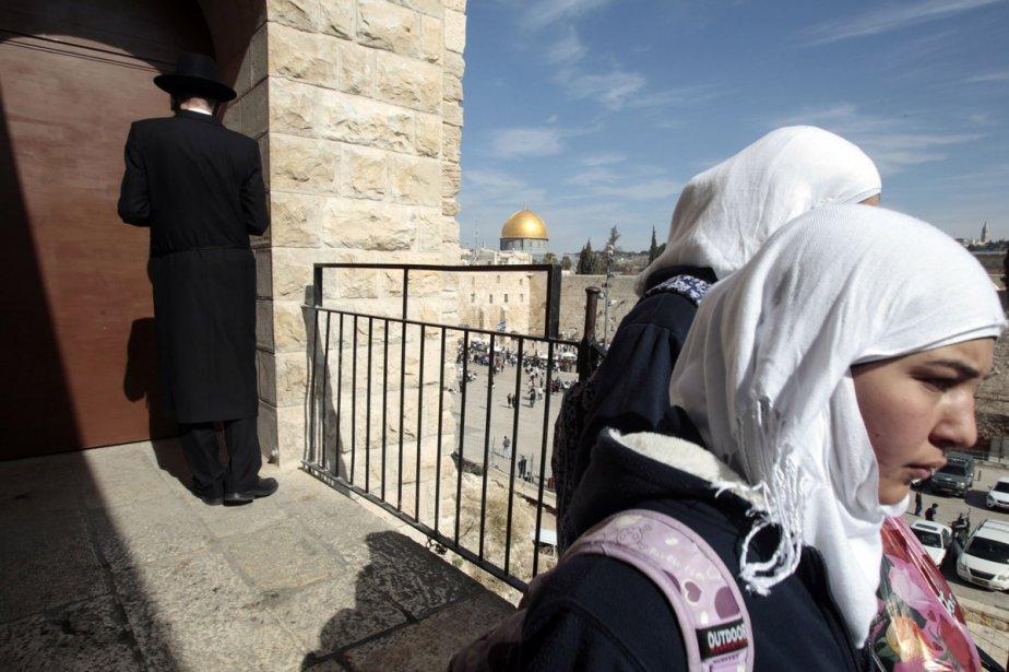 De jeunes étudiantes palestiniennes croisent un Juif ultra-orthodoxe... (Photo: Reuters)