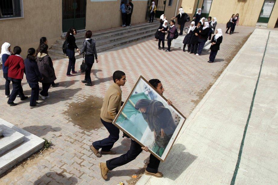 Des écoliers se dépêchent de transporter un portrait... (Photo: Reuters)