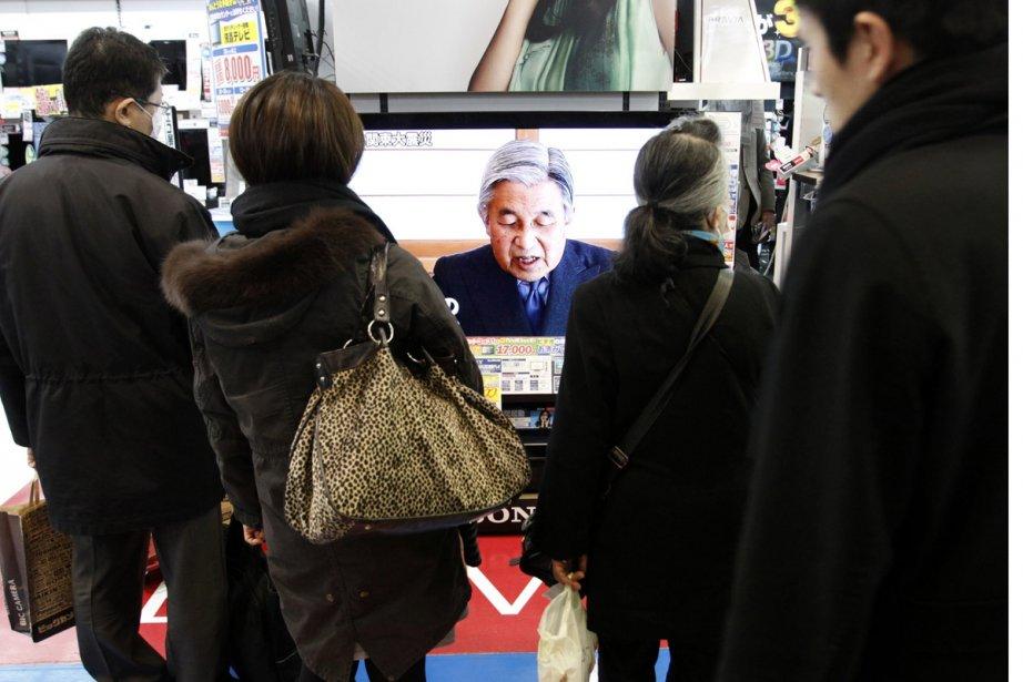 Des Japonais se sont arrêtés devant la télévision... (Photo: AFP)