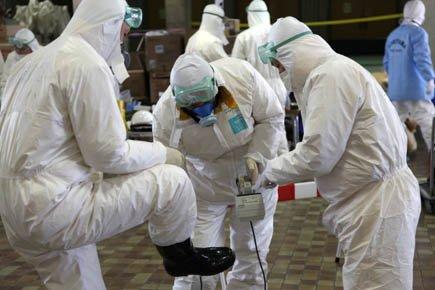 Les membres d'une équipe de spécialistes en radioactivité... (Photo: AFP)