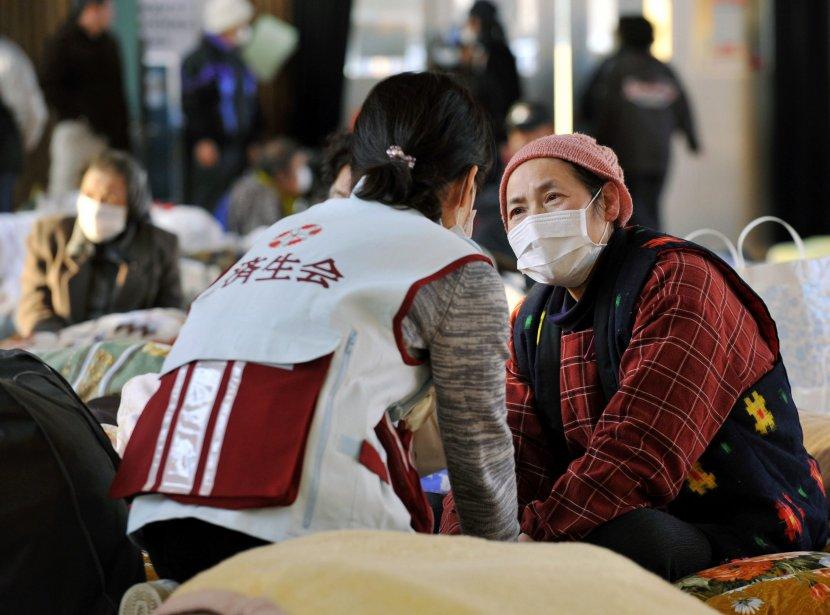 Les Japonais, affligés par une triple catastrophe, séisme,... (PHOTO: KYODO NEWS, AP)