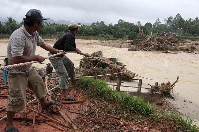 Des villageois thaïlandais tentent de réparer un pont... (Photo: Reuters)