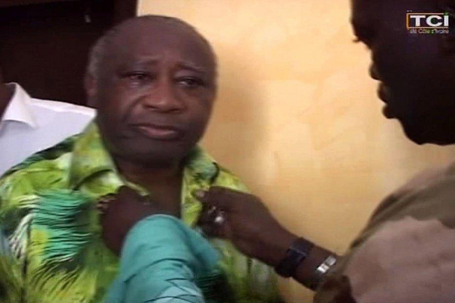 Un militaire boutonne la chemise de Laurent Gbagbo... (Photo: AFP)