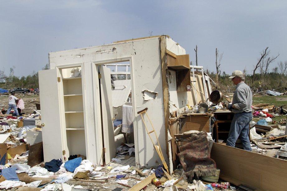 Henry Alston nettoie ce qui reste de la maison de son père en Caroline du Nord. (Photo AP)