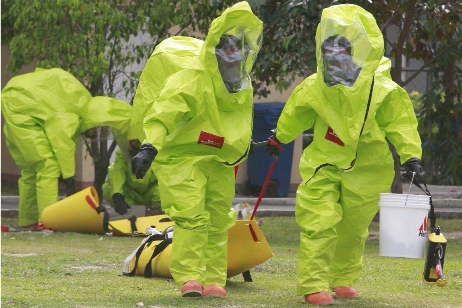 Des travailleurs philippins, vêtus de combinaisons protectrices, participent... (Photo: Reuters)