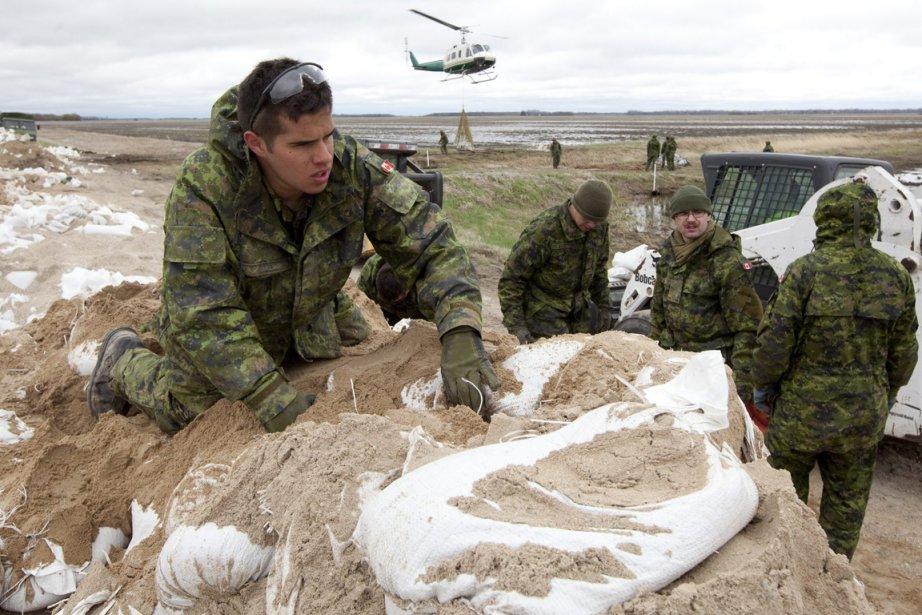 Des militaires transportent des sacs de sable qui... (Photo: PC)