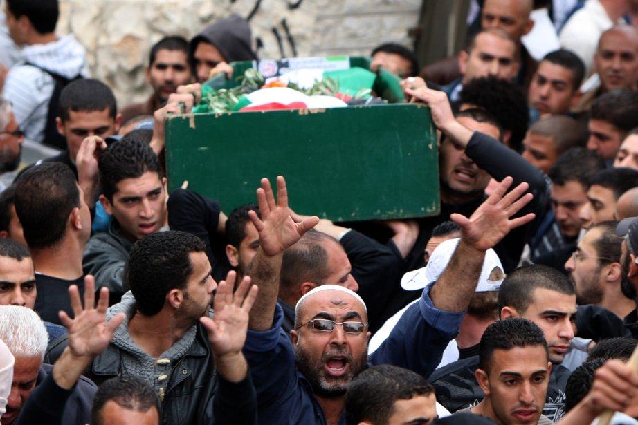 Le corps de l'adolescent palestinien est porté lors... (Photo AFP)
