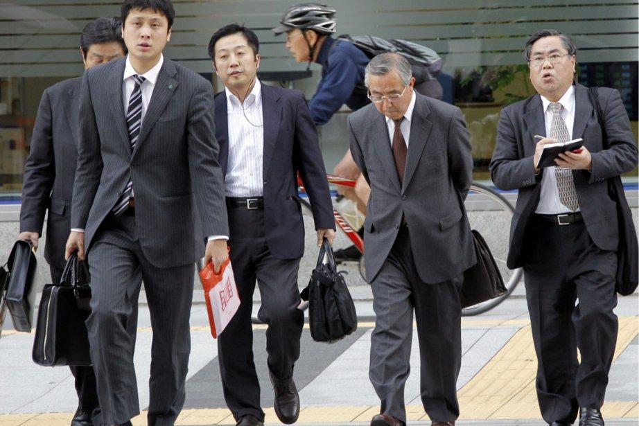 Des hommes d'affaires japonais dans une rue de... (Photo AP)