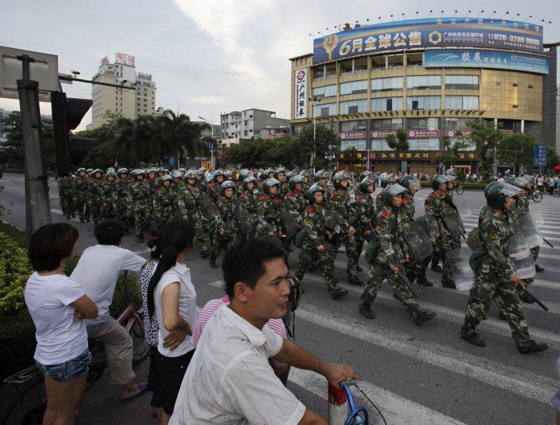Des résidants regardent les policiers anti-émeutes défilés dans les rues. | 15 juin 2011