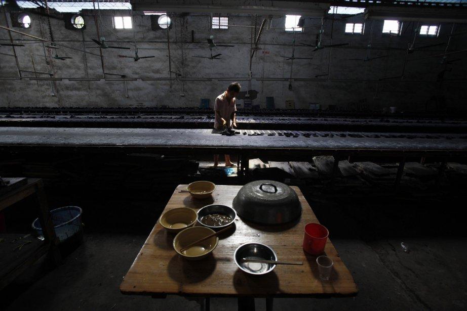 Un travailleur migrant ramasse des étiquettes dans une manufacture de jeans dans le village de Dadun près de Xintang. | 15 juin 2011
