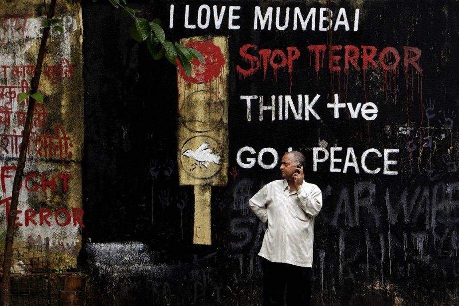 Un homme parle au téléphone devant un graffiti... (Photo: Aijaz Rahi, AP)