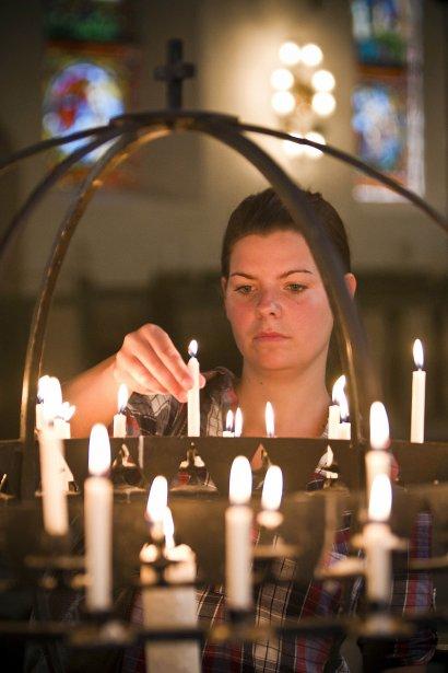 Une jeune femme allume des chandelles samedi. | 23 juillet 2011