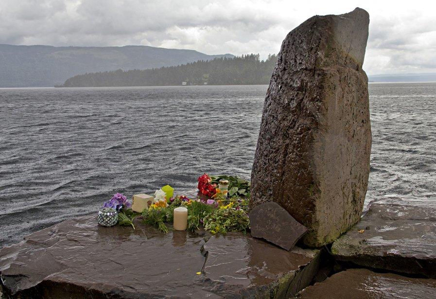 Des fleurs ont été déposées sur un rocher à l'île d'Utoya où une fusillade a fait au moins 68 morts. | 24 juillet 2011