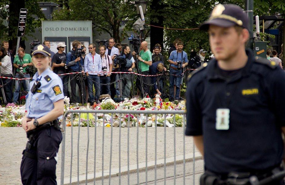 Des gens ont déposé des fleurs près du site de l'explosion à Oslo. La police gardait un large périmiètre dimanche. | 24 juillet 2011