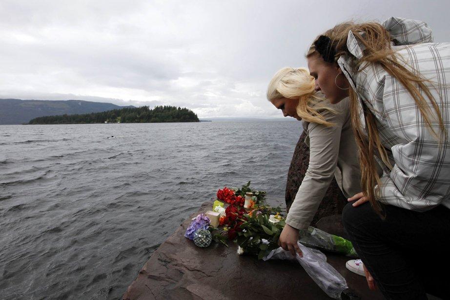 Deux jeunes femmes déposent des fleurs à l'île d'Utoya où une fusillade a fait au moins 85 morts. | 24 juillet 2011