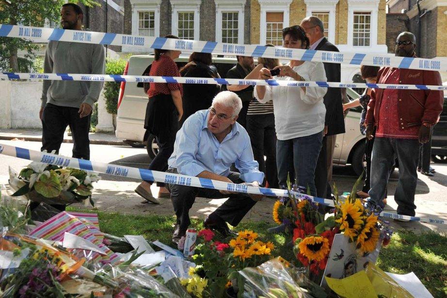Mitch (accroupi au centre) et Janis Winehouse (au centre tenant un appareil photo) père et mère de la chanteuse Amy Winehouse décédée ce weekend devant les fleurs, les photos et les messages laissés en hommage à la diva du soul et du jazz. (Photo: AFP)