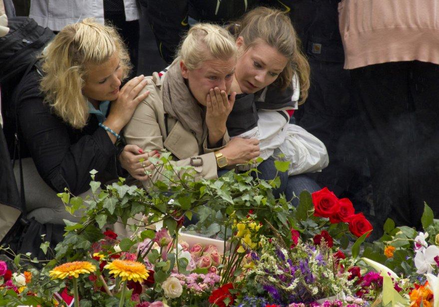 Des Norvégiennes se recueillent devant le parterre de fleurs à l'entrée de la cathédrale d'Oslo. | 26 juillet 2011