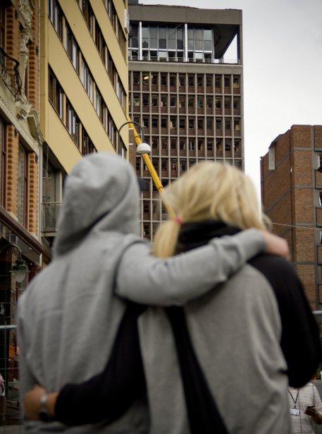 Deux jeunes Norvégiens regardent  l'édifice du siège du gouvernement qui a été la cible d'une attaque à la bombe orchestrée par Anders Breivik. | 26 juillet 2011