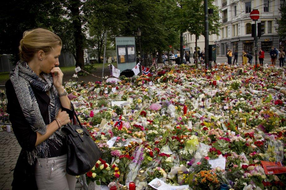 Une jeune Norvégienne regarde avec émotion le parterre de fleurs à l'entrée de la cathédrale d'Oslo. | 26 juillet 2011