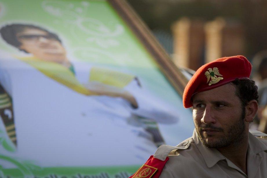 Un soldat libyen est vu devant un portrait... (Photo: Caren Firouz, Reuters)